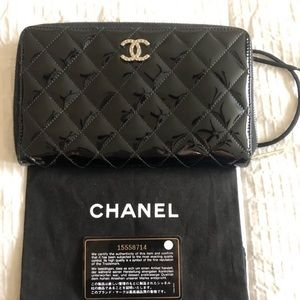 CHANEL Black, quilted patent leather wallet.